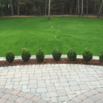 Hardscaping: Stone-brick patio lined with mini-shrubs and mulch - Greener Horizon