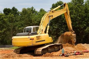 Backhoe machine uses shovel scooper to excavate and move dirt.