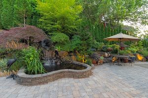 Backyard garden landscaping with waterfall and pond with hardscaping.