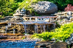 Backyard landscaping with pondless water feature.