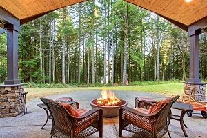 Large backyard, two chairs around a firepit on hardscape looking at the woods.